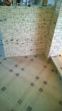 На пол положили плитку, все стыки и углы аккуратно отделаны